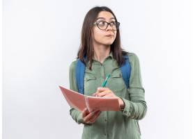想法的年轻学校妇女戴眼镜与背包写东西在笔_17415576