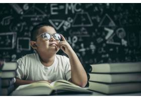 戴眼镜的男孩写书在教室里思考_10039063