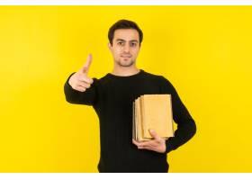 拿着在黄色墙壁上的年轻人画象学院书_17289463