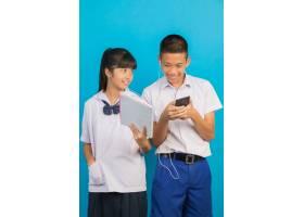拿着笔记本和站立在蓝色的亚洲男学生的亚裔_5601700