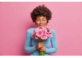 有吸引力的令人高兴的黑皮肤模型接受着鲜花_13666378