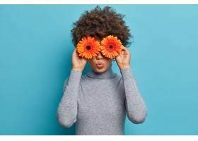 有鲜花的可爱的浪漫少妇在眼前保持嘴唇圆_13666957