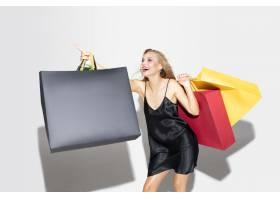 购物在白色背景的黑礼服的年轻白肤金发的妇_17245544