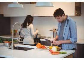 砍菜的人在厨房里当烹调食物的妇女在背景_9597776
