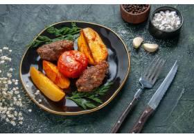 可口肉炸肉排侧视图烘烤用土豆和蕃茄在黑色_17247327