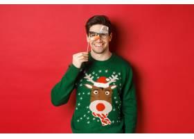 圣诞节毛线衣和党面具的滑稽的人庆祝寒假_17395672