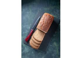 黑面包顶视图切片在深色委员会的刀子在蓝色_17247433