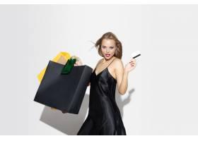 购物在白色背景的黑礼服的年轻白肤金发的妇_17245555