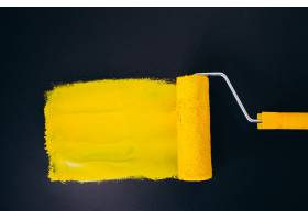在黑背景隔绝的修理的漆滚筒在黄色油漆_7377646