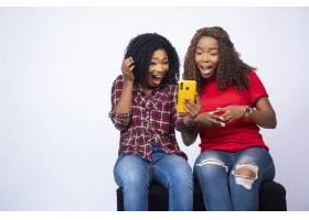 射击看电话的两个年轻黑人女性感觉激动和惊_17248256