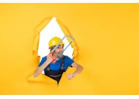 在拿着在黄色背景的制服的前面看法男性建造_16609599