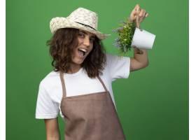 拿着在花盆的制服佩带的从事园艺的帽子的快_13959000