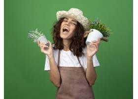 拿着在花盆的制服佩带的从事园艺的帽子的激_13959309