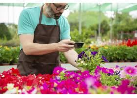 射击盆的植物的男性花匠裁剪看法在手机_13996111