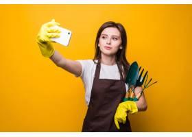 少妇花匠采取在电话的selfie当拿着工具被_13814249