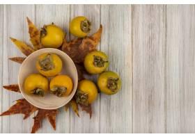 未成熟的柿子果子顶视图在一个碗的有叶子的_13997408