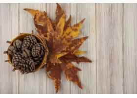 杉木锥体顶视图在一个桶的与在一张灰色木桌_13997008
