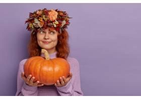 可爱的梦幻女人抱着大成熟的南瓜看起来奇_12701054