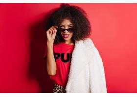 外套和太阳镜的肉欲的妇女站立在红色墙壁上_12304720