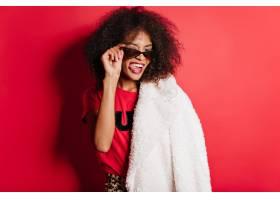太阳镜的高兴的妇女做在红色墙壁上的面孔_12304721