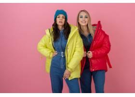 两个兴奋的有吸引力的女朋友摆在桃红色墙壁_12152486