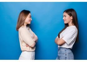 两个高兴的女孩在蓝色的墙上互相看_14670566