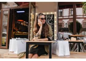 乏味妇女在购物以后坐在室外咖啡馆时叫某人_10786667