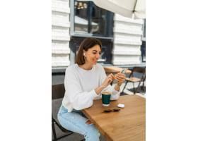 享受在咖啡馆的俏丽的短发妇女室外画象在咖_16792922