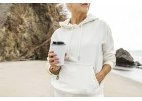 享受她的早晨咖啡的资深妇女在海滩_15438506