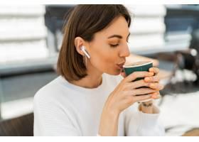 享受热奶咖啡的漂白的短发妇女在咖啡馆穿_16793104