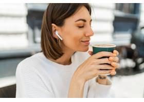 享受热奶咖啡的漂白的短发妇女在咖啡馆穿_16793181