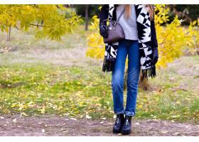 亭亭玉立的妇女穿在秋天森林里的蓝色牛仔裤_10067992