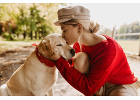 亲吻她可爱的狗的美丽的白肤金发的女孩在秋_12018410