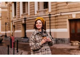 黄色贝雷帽的微笑的妇女喜欢在城市走路_12858160