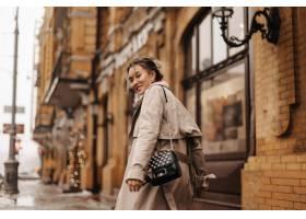 高精度的年轻亚裔妇女在时髦的风衣的城市走_12860450