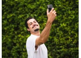 采取selfies的深色男性反对绿色植物_15985911