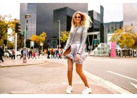 退出的幸福的金发女郎跳舞和在现代大厦的街_9855515