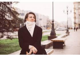 穿黑冬天外套和围巾的白种人妇女室外画象坐_13437414