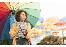 笑的妇女散步户外与彩虹伞_9853656