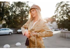 米黄盖帽和夹克的时髦的白肤金发的妇女走在_10578628
