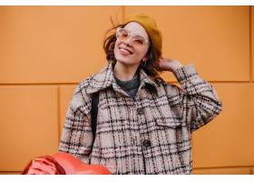 粗呢外套的正面妇女与摆在橙色墙壁上的微笑_12858196