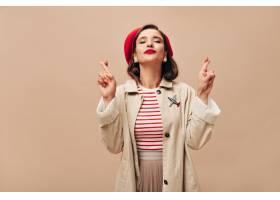 红色贝雷帽和米黄沟槽的愉快的妇女横渡手指_13212074