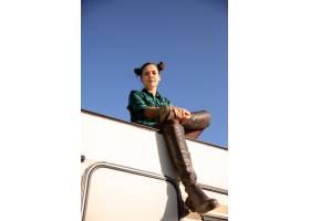 看下来和坐一台减速火箭的露营车的屋顶的女_17332751