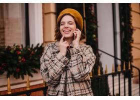 橙色贝雷帽和外套的正面妇女笑当谈话在电_12858190