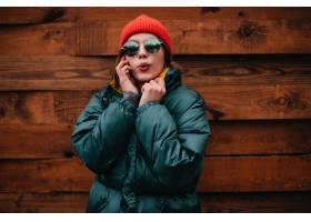明亮的冬天成套装备的逗人喜爱的妇女在电话_12858209