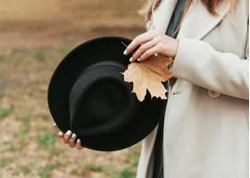 拿着她的黑帽子和叶子特写镜头的兴高采烈的_9859263