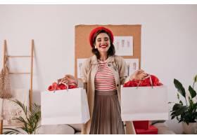 拿着白色购物袋的红色贝雷帽的迷人的妇女_13212495