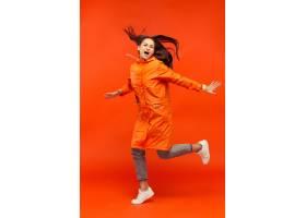 摆在秋天橙色夹克的演播室的愉快的微笑的女_12836942