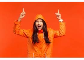 摆在秋天橙色夹克的演播室的愉快的微笑的女_13055471