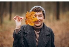 拿着叶子的秋天公园的少妇由面孔_12178052